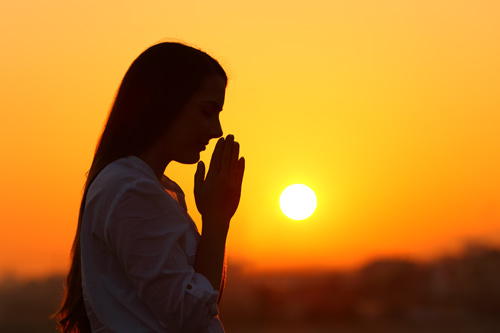woman praying with sunset in background