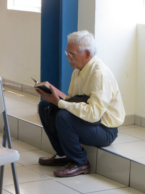 Man in El Salvador sitting and reading Bible with new eyeglasses.