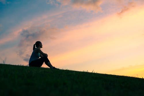 woman sitting on hill, watching sunrise
