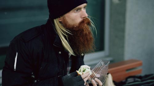 homeless man eating a sandwich