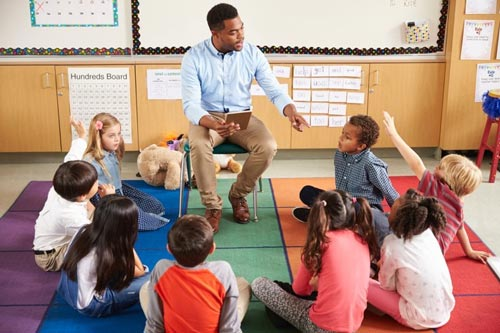 teacher with young children sitting in a semi-circle around him