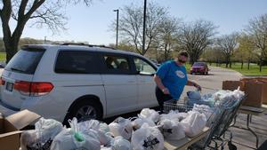 woman loading bags of food into van