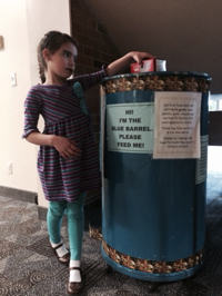 child putting food in the blue barrel